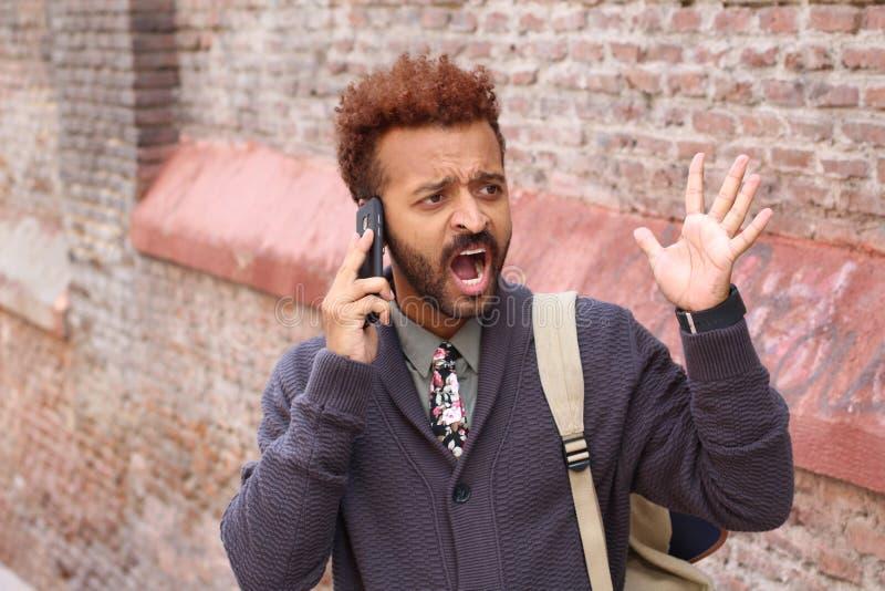 Nieszczęśliwy przedsiębiorca krzyczy podczas rozmowy telefonicza obraz stock