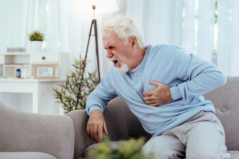 Nieszczęśliwy starszy mężczyzna ma chorobę sercowo-naczyniową zdjęcie stock