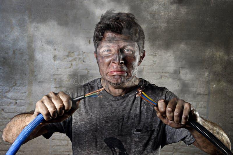 Nieszkolony mężczyzna łączy kablowego cierpienia elektrycznego wypadek z brudnym burnt twarz szokiem wyrażeniowym obrazy stock