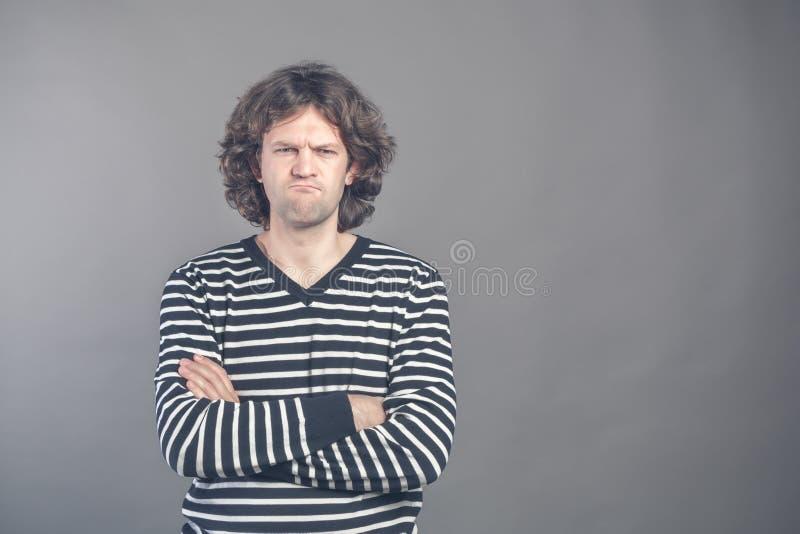 Niet bevallene close-up het portret, de boze knorrige mens in gestreepte sweater slechte houding die, gekruiste wapens, gevouwen, royalty-vrije stock foto