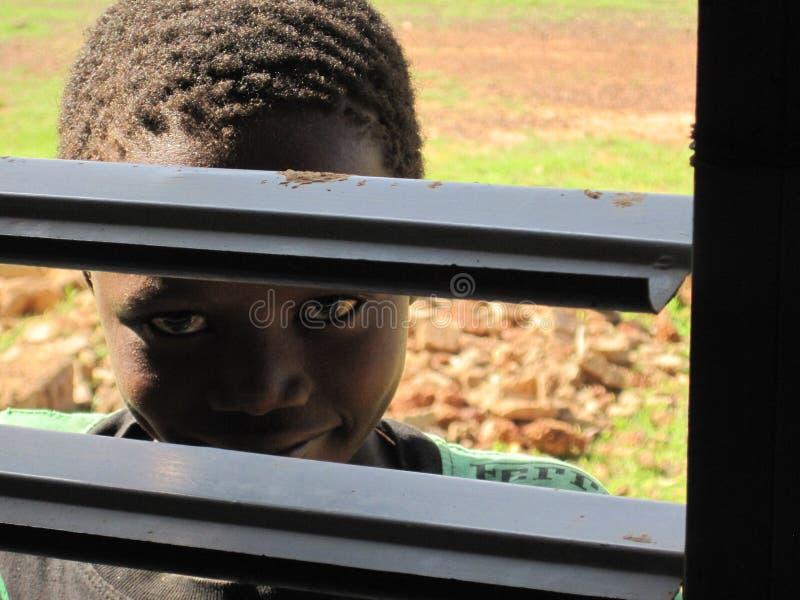 Niet geïdentificeerd kind die door venster van de school van de liefdadigheidslooppas in Burkina Faso turen royalty-vrije stock foto's