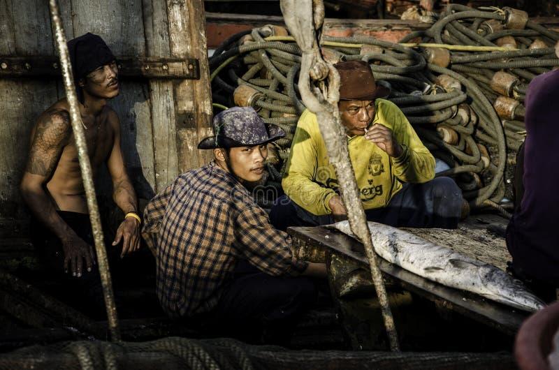 Niet geïdentificeerde arbeidersrust in vissersboot royalty-vrije stock afbeeldingen