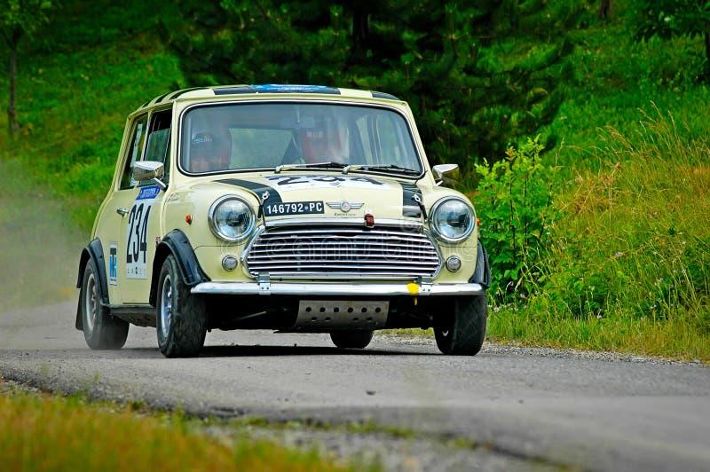 Niet geïdentificeerde bestuurders op een gele uitstekende Mini Cooper-raceauto stock foto
