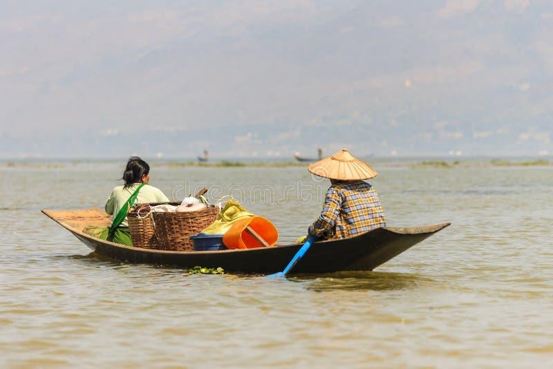 Niet geïdentificeerde Birmaanse visser op bamboeboot die vissen op traditionele manier met met de hand gemaakte netto vangt royalty-vrije stock afbeeldingen