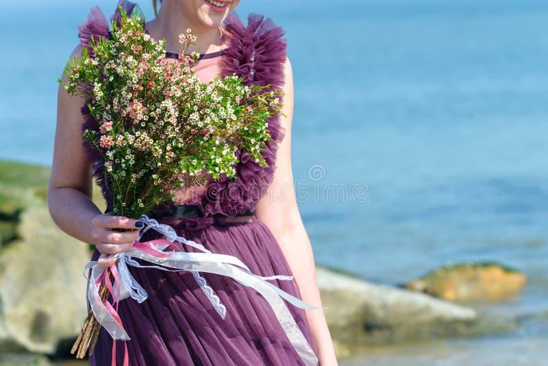 Niet geïdentificeerde bruid die in mooie huwelijkskleding zachte nic houden stock afbeelding