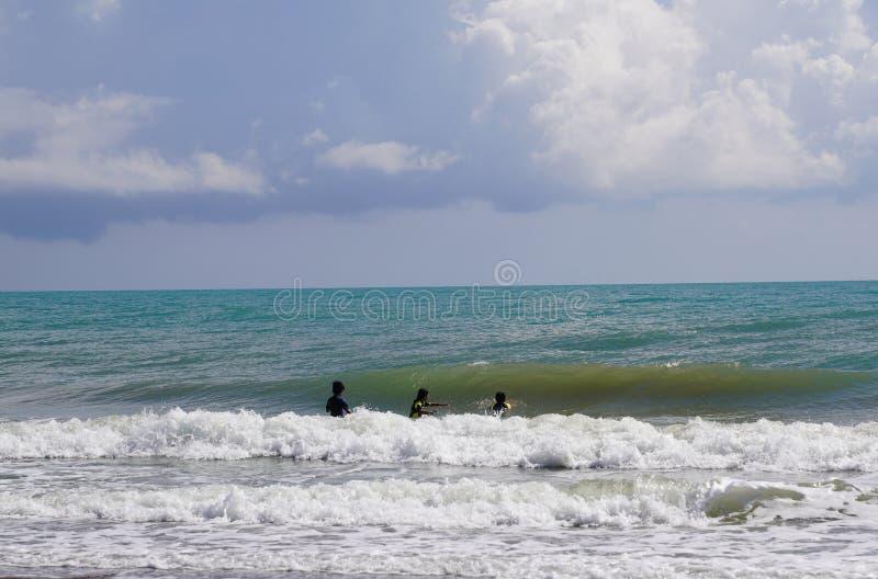 Niet geïdentificeerde drie kinderen die van golvend Middellandse-Zeegebied genieten royalty-vrije stock foto