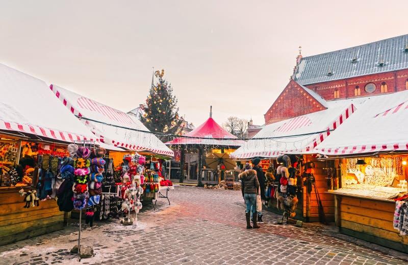Niet geïdentificeerde groep die mensen herinneringen kiezen bij Kerstmismarkt in de winter Riga in Letland stock foto's