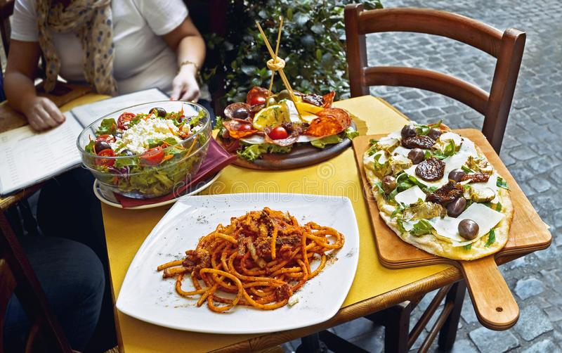 Niet geïdentificeerde mensen die traditioneel Italiaans voedsel in openluchtrestaurant eten stock afbeelding