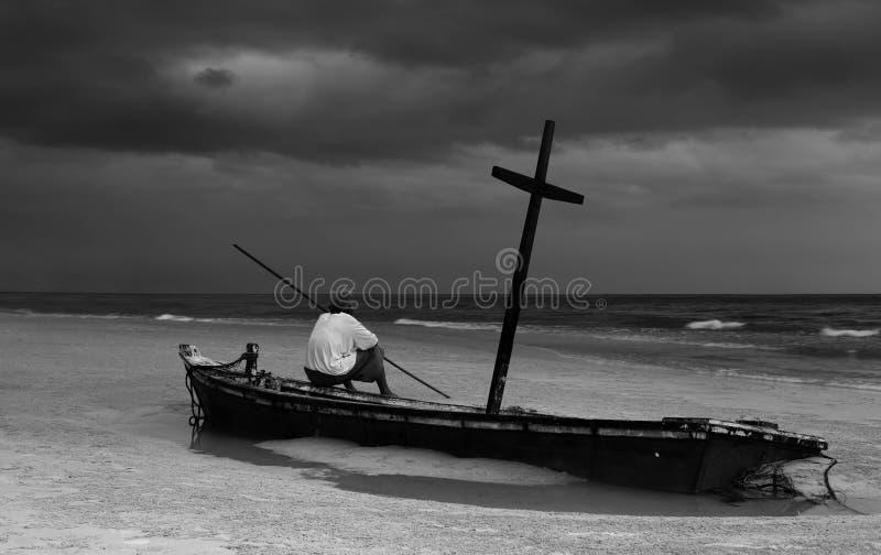 Niet geïdentificeerde oude mens op wereckboot op het strand met onweersclou stock foto