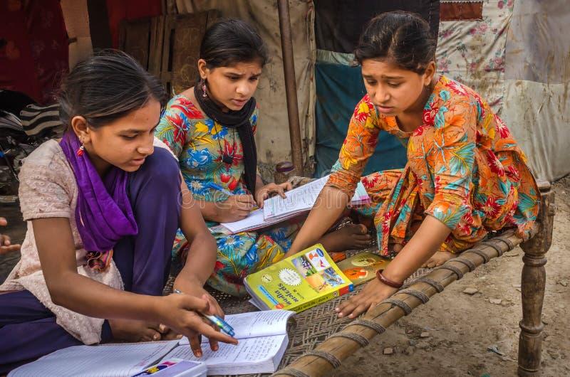 Niet geïdentificeerde schoolmeisjes van Indisch het Behoren tot een bepaald ras bezig het doen thuiswerk stock foto
