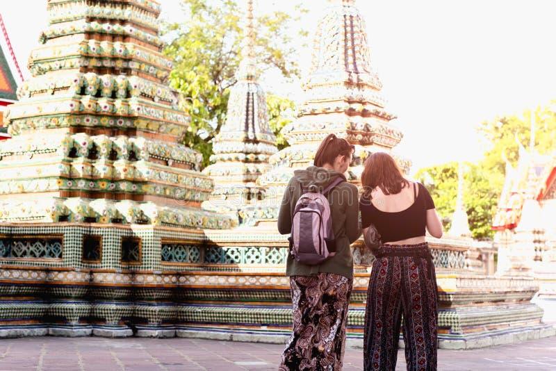 Niet geïdentificeerde toeristenvrouwen die Thaise tempel achtermening in Bangkok Thailand bezoeken stock afbeeldingen