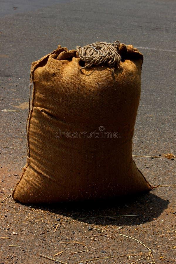Niet gepolijste die Rijstzaden in zak worden ingepakt stock afbeeldingen