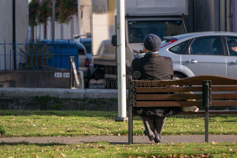 Niet identificeerbare eenzame oude mensenzitting op een parkbank die een pijp roken royalty-vrije stock fotografie