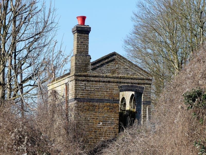 Niet meer gebruikte en verlaten die spoorweg met rode emmer bovenop schoorsteen, Chorleywood wordt afgeworpen stock afbeeldingen