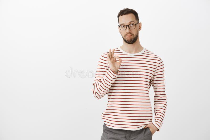 Niet slecht, als uw idee, goede baan Tevreden geïmponeerde aantrekkelijke rijpe kerel in glazen en gestreepte kleren, die o.k. to royalty-vrije stock foto
