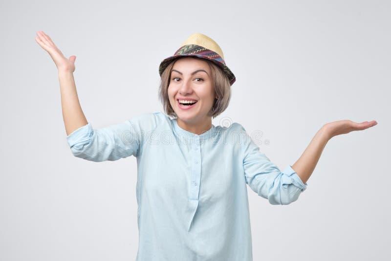 Niet zeker, geen mijn probleem De gelukkige jonge volwassen vrouw met deelt uit, ophalend haar schouders stock foto's