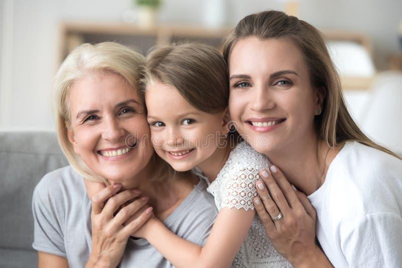 Nieta diversa y abuela de la hija de la generación tres que miran la cámara imagenes de archivo