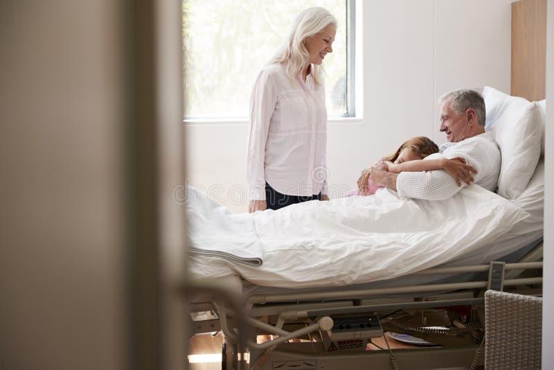 Nieta que abraza al abuelo en visita del hospital de la familia fotografía de archivo libre de regalías