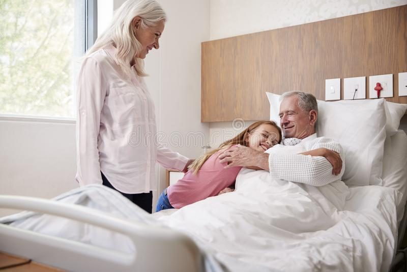Nieta que abraza al abuelo en visita del hospital de la familia foto de archivo