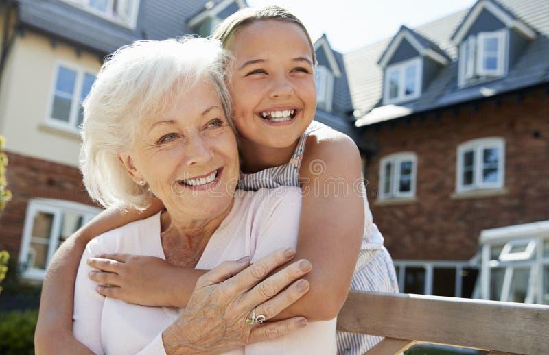 Nieta que abraza a la abuela en banco durante visita a la casa de retiro fotos de archivo libres de regalías