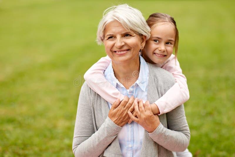 Nieta que abraza a la abuela en el parque del verano foto de archivo libre de regalías
