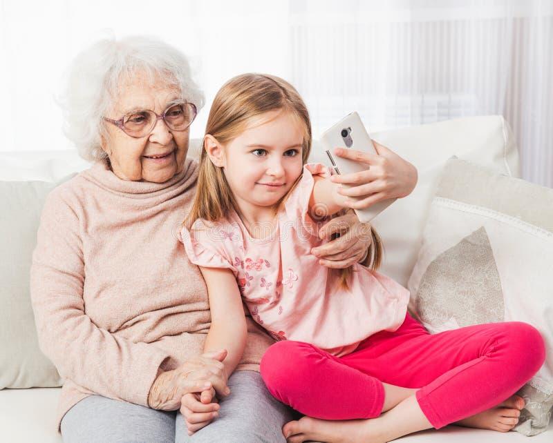 Nieta que toma el selfie con la bisabuela imagen de archivo