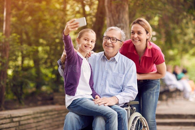 Nieta que usa el teléfono para el selfie con su padre discapacitado adentro imágenes de archivo libres de regalías