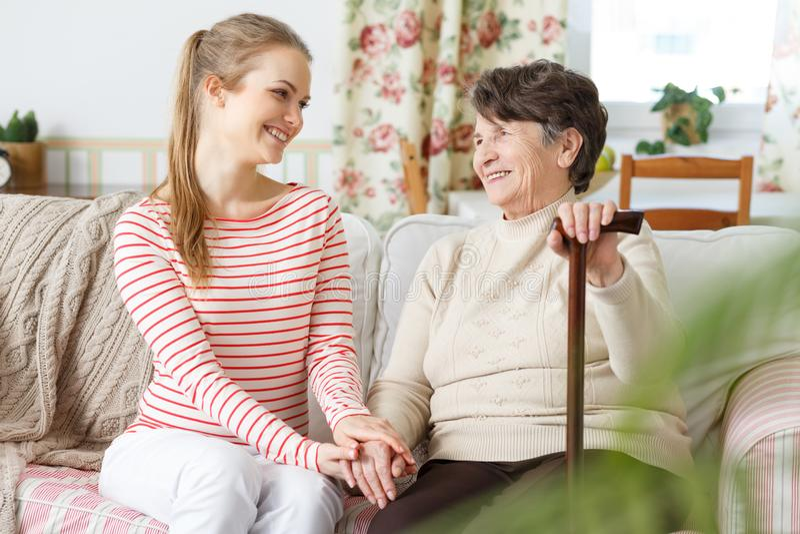 Nieta y abuela que se sientan en un sofá imagenes de archivo