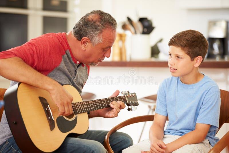 Nieto de enseñanza de abuelo para tocar la guitarra foto de archivo libre de regalías