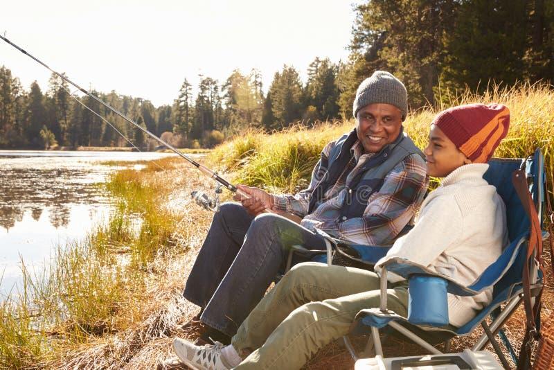 Nieto de enseñanza de abuelo a pescar por el lago imágenes de archivo libres de regalías
