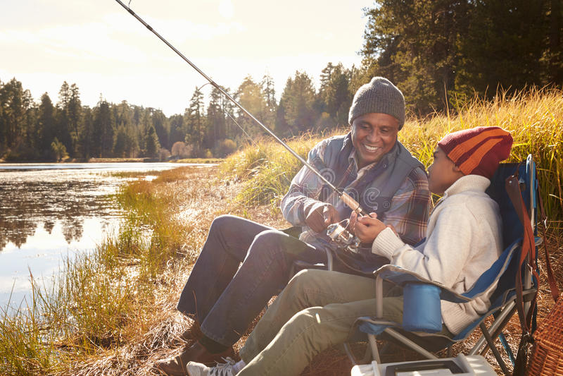 Nieto de enseñanza de abuelo a pescar por el lago fotografía de archivo