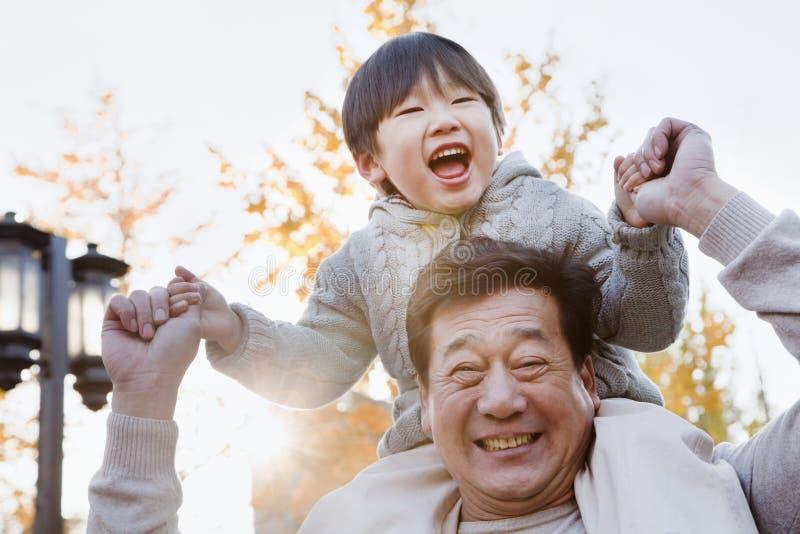 Nieto de risa que lleva del abuelo en sus hombros fotos de archivo