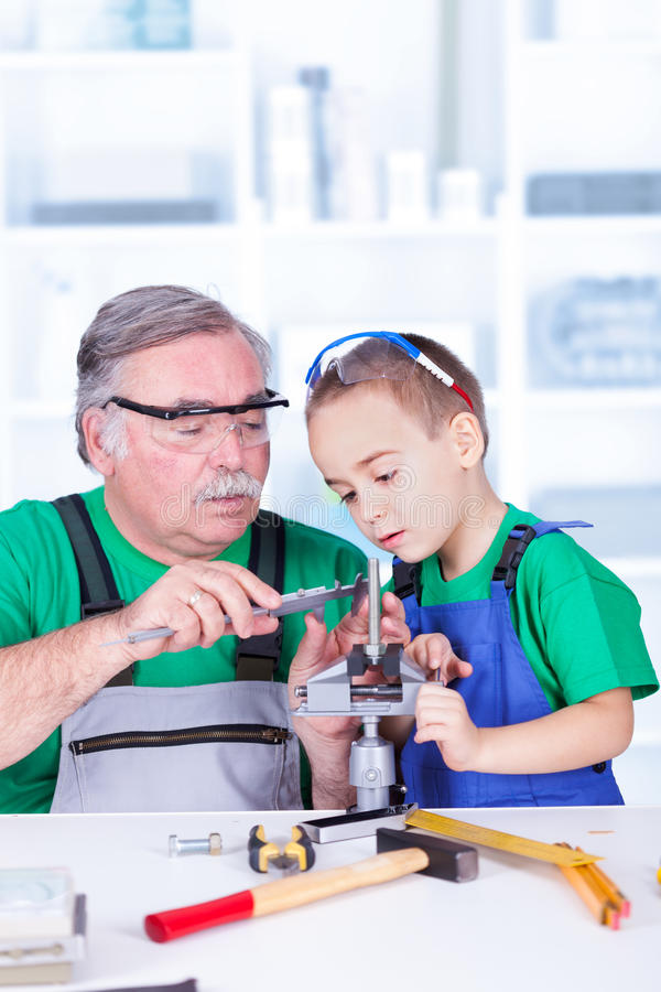 Nieto que muestra de abuelo el calibrador a vernier foto de archivo libre de regalías