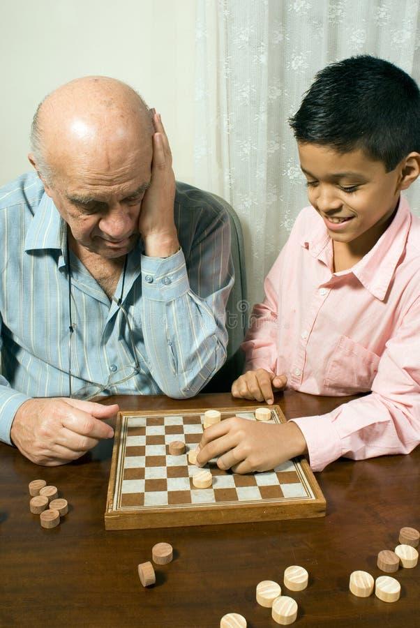 Nieto y abuelo que juegan a ajedrez imagen de archivo libre de regalías