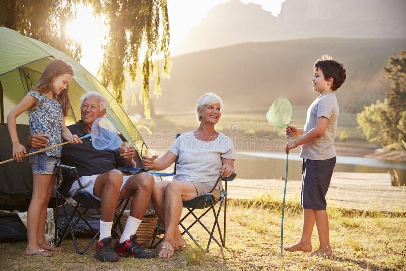 Nietos con los abuelos en acampada por el lago imagen de archivo