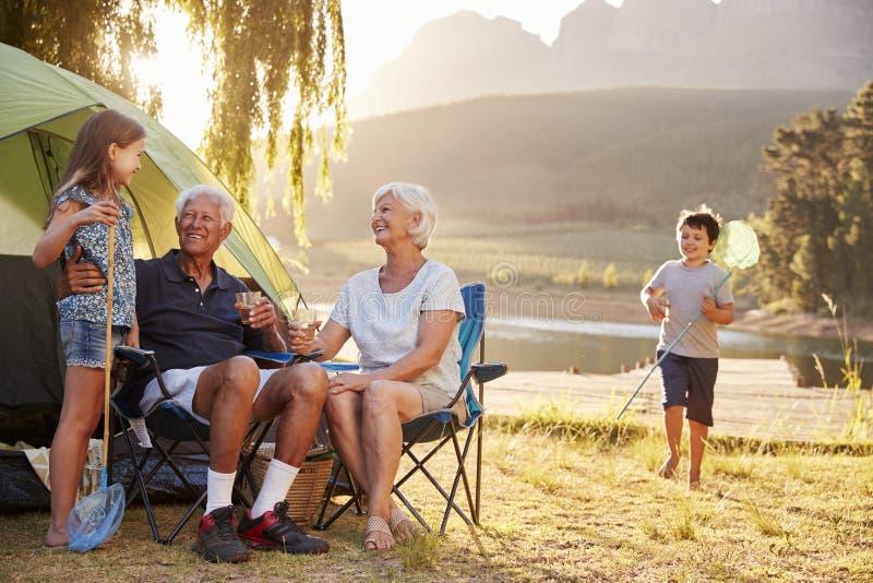 Nietos con los abuelos en acampada por el lago fotografía de archivo libre de regalías