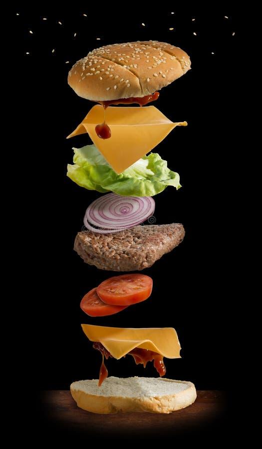 Nieuporządkowany hamburger z wszystkie składnikami które latają fotografia royalty free