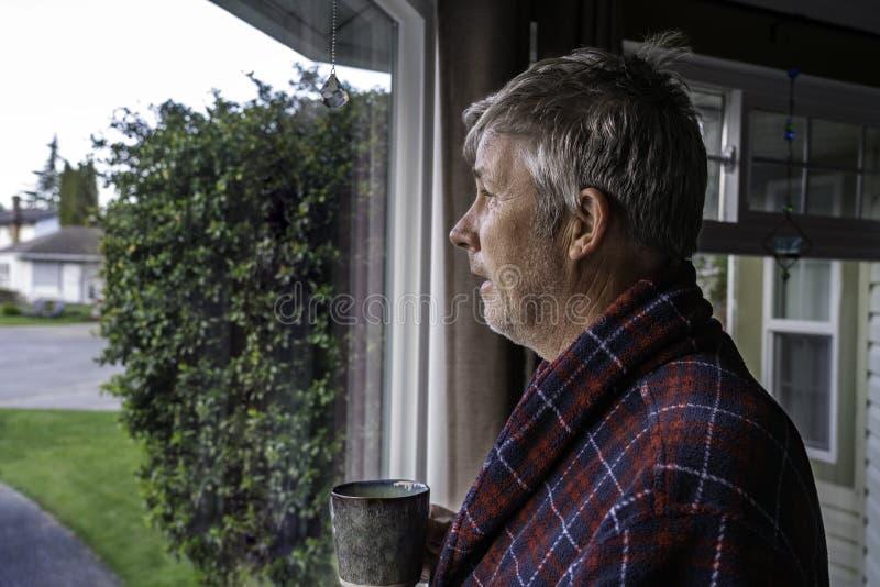 Nieutrzymany starszy mężczyzna z głową w kurtce, patrzący przez okno zdjęcie royalty free