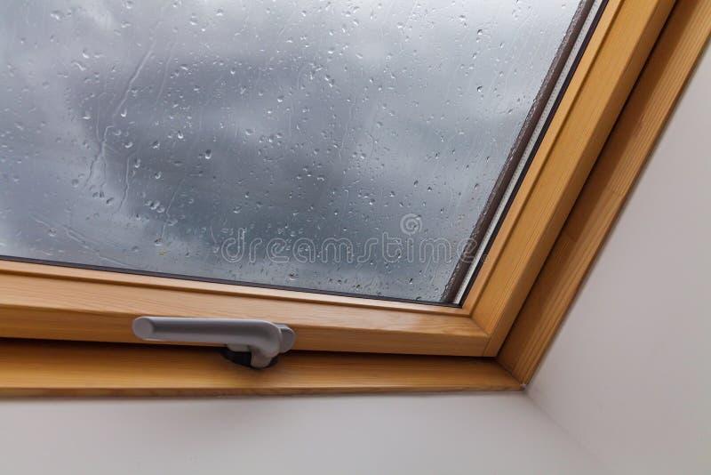 Nieuw dakvenster tijdens de regens met dalingen op het glas stock foto's