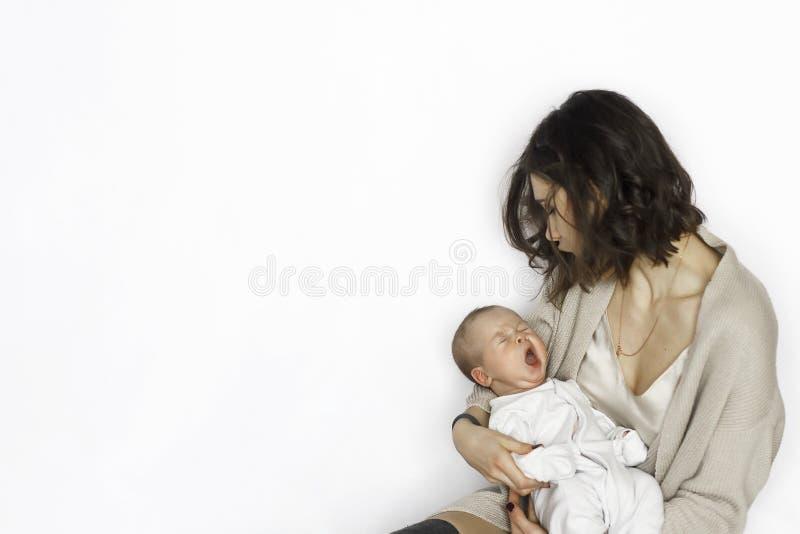 Nieuw - de geboren slaap van de babyjongen, die op moeder` s wapen gieren stock fotografie
