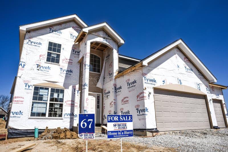 Nieuw die huis gedeeltelijk, in aanbouw in woonhuisvestingsonderverdeling wordt gebeëindigd met voor verkoopteken in werf stock afbeeldingen
