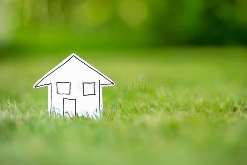 Nieuw document huis in gras stock afbeelding
