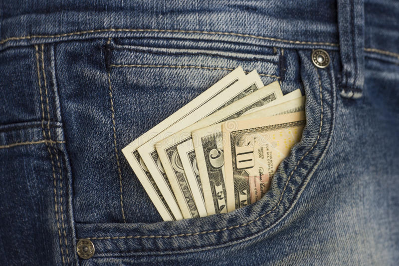 Nieuw dollarbroodje in heupzak van versleten jeansclose-up royalty-vrije stock foto