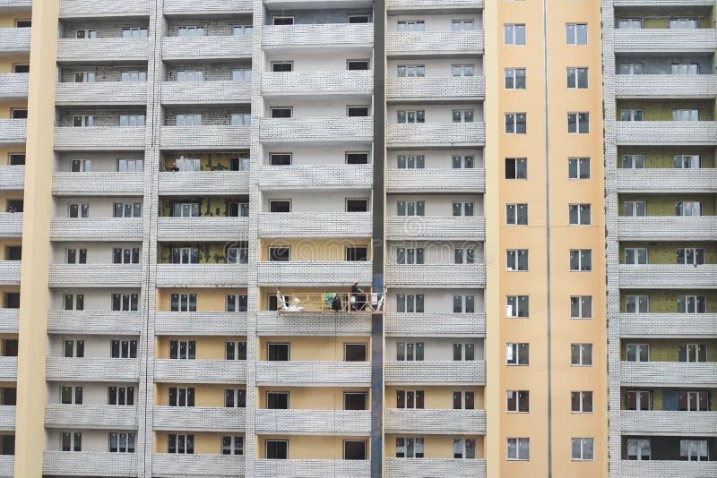 Nieuw flatgebouw in aanbouw De bouwers pleisteren muren stock fotografie