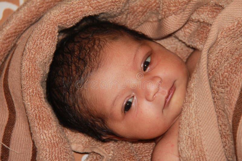 Nieuw - geboren Aziatisch babymeisje dat in een handdoek wordt verpakt stock foto