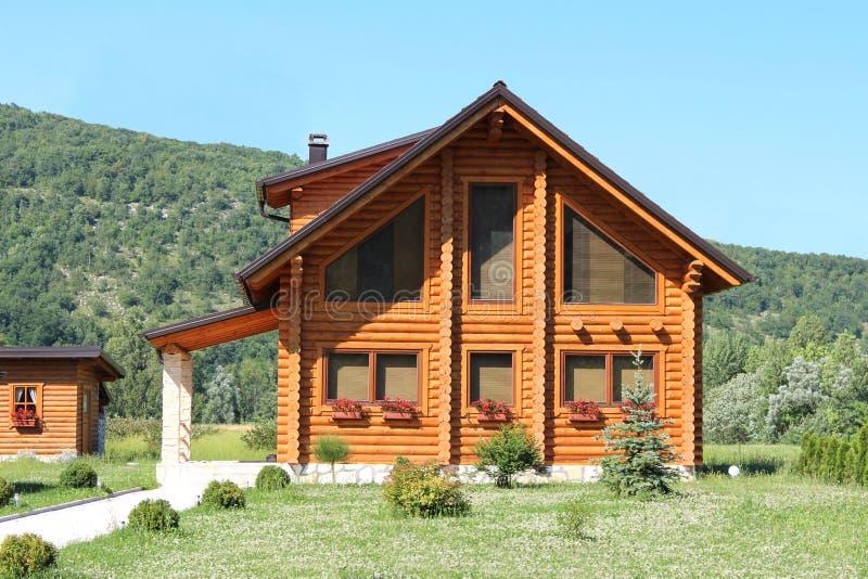 Nieuw houten die blokhuishuis met gras en bos wordt omringd stock afbeeldingen