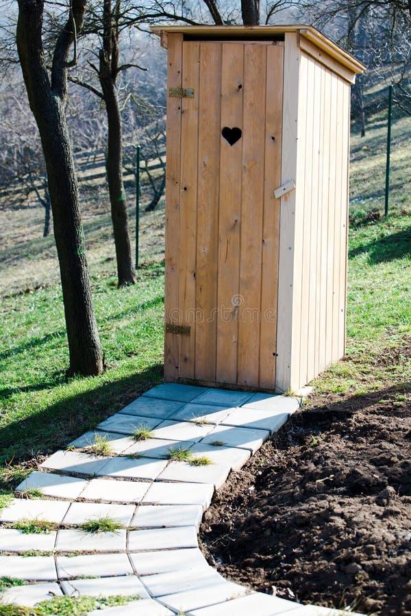 Nieuw houten toilet in de tuin - het Hart gaf gat op de deur gestalte royalty-vrije stock foto's