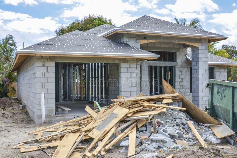 Nieuw huis en bouwpuin stock fotografie