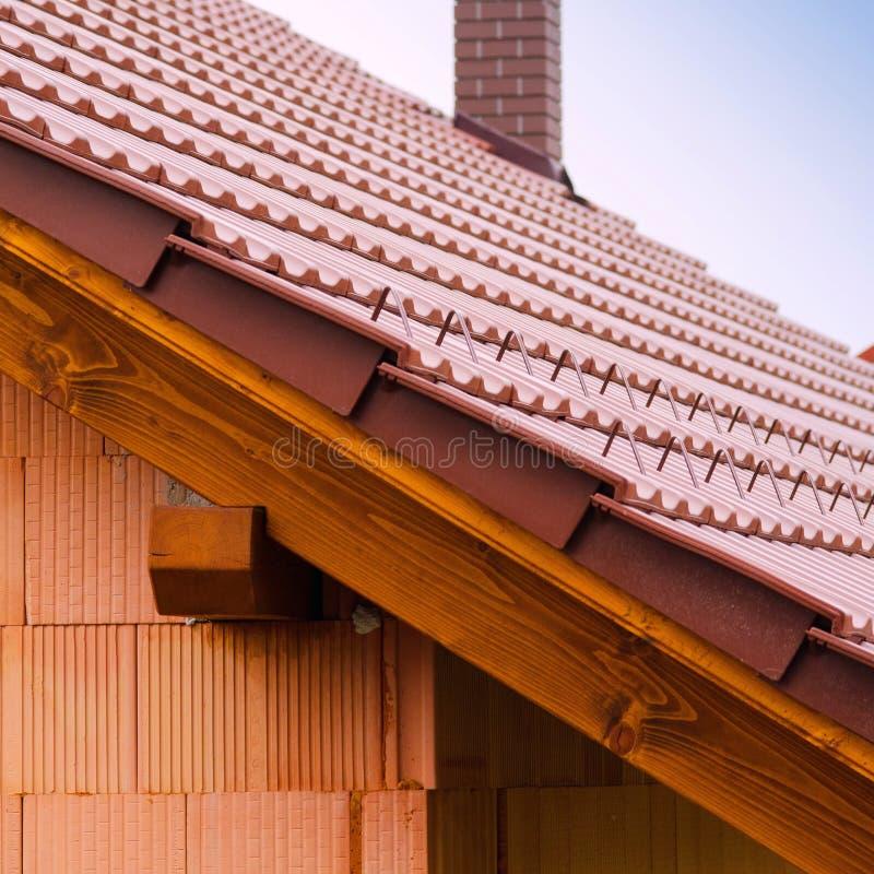 Nieuw huis met oranje bakstenen muur, dak en schoorsteen Het concept van de woningbouwarbeider stock afbeeldingen