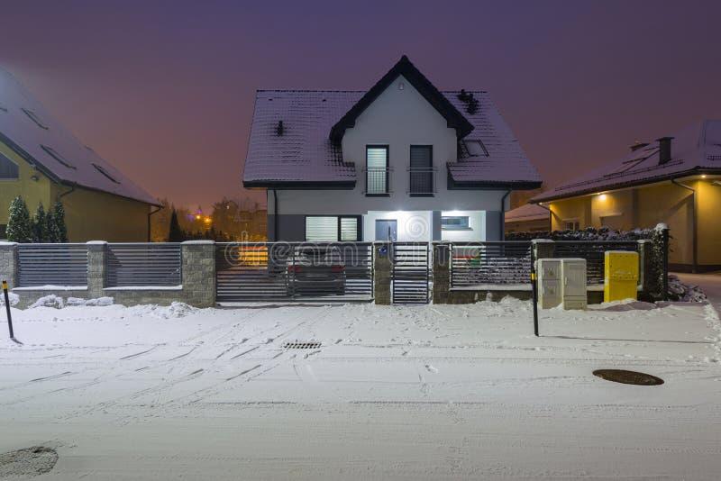 Nieuw huis met steenomheining bij sneeuwnacht stock fotografie